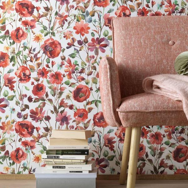 Vliestapete mit üppigem Blumenwiesenmuster in rot und grünen Farbtönen gehalten. Im Vordergrund Sessel in zartem Rosa