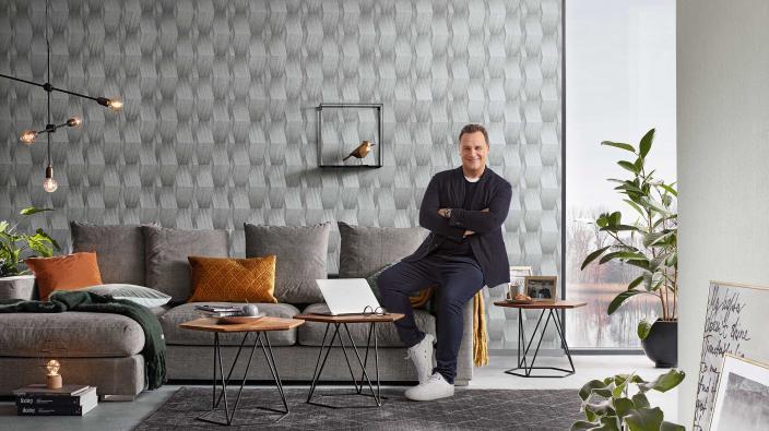 Guido Maria Kretschmer in modernem Wohnzimmer mit 3D Vliestapete in Silbergrau