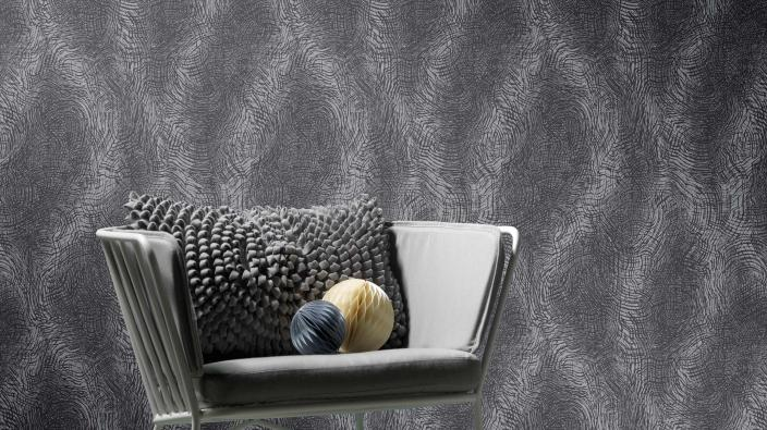 Vliestapete mit irrisierenden Wellen in Grau- und Silbertönen, moderner Sessel in Grau