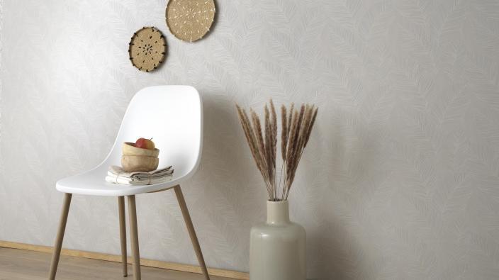 cremefarbene Vliestapete mit Blättermotiv, weißer Stuhl und Accessoires im Boho-Look