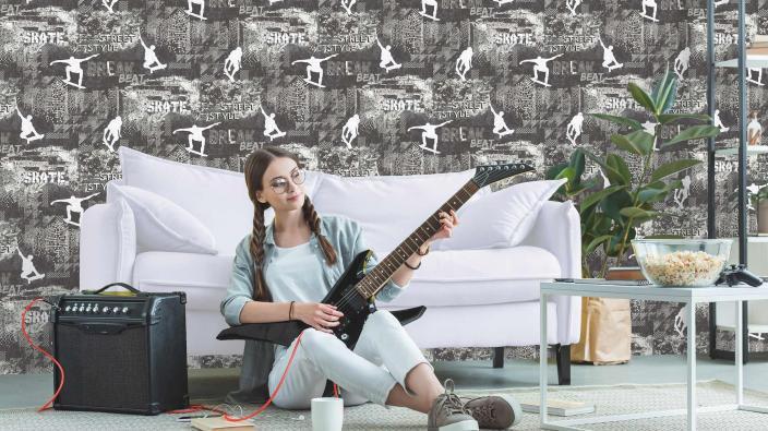 Jugendzimmer, Sofa, Mädchen mit E-Gitarre, coole Vliestapete mit Skatern und Skyline