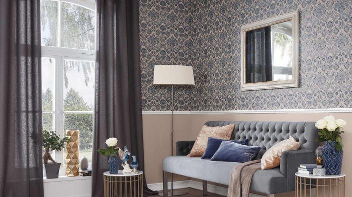 Eleganter Wohnraum mit Barock Vliestapete in Grau-Taupe. Graues Sofa, Porzellan-Deko, Stehlampe, Spiegel