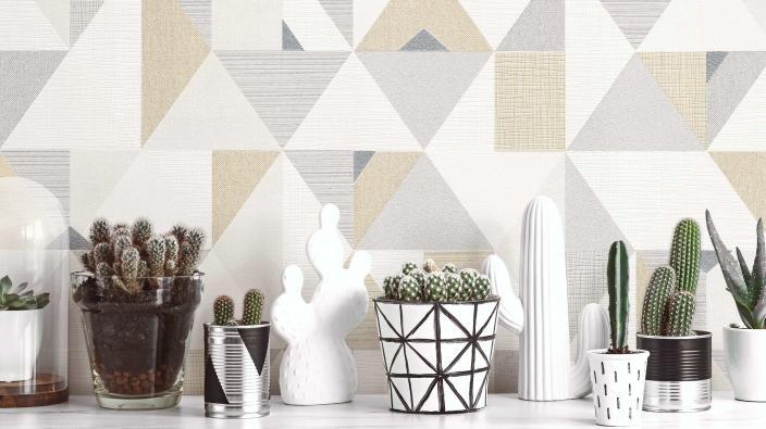 Wandgestaltung mit Vliestapete in hellem Taupe und Creme, grafisches 3D-Muster mit Dreiecken, Sideboard mit Kakteen