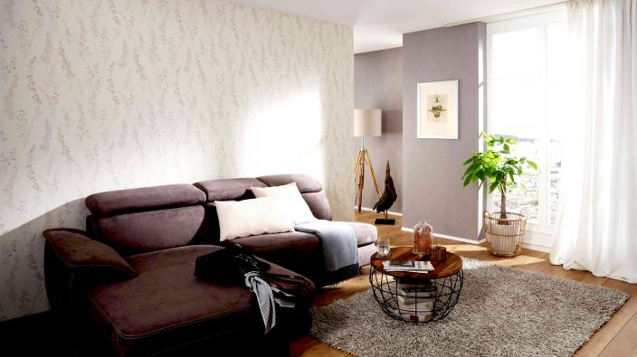 Vliestapete Kollektion Darling, cremefragiges Blumenmuster mit taupem Uni, grauer Couch mit Holztisch und Zimmerpflanze