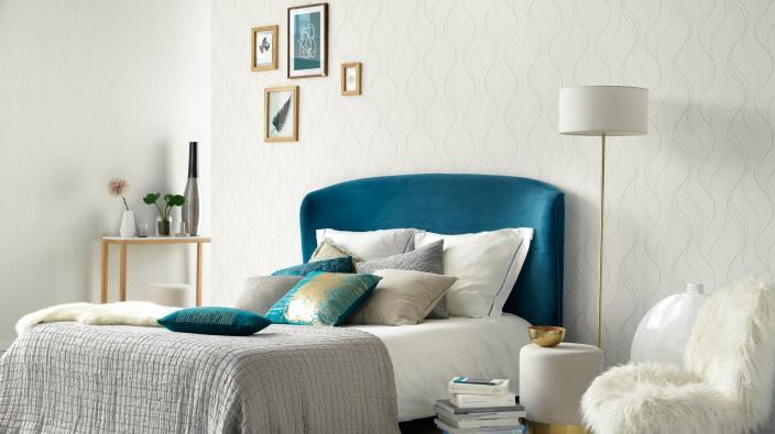 Wandgestaltung Schlafzimmer, weiße Vliestapete mit Wellenmuster, Bett blau, Dekokissen, Lampe
