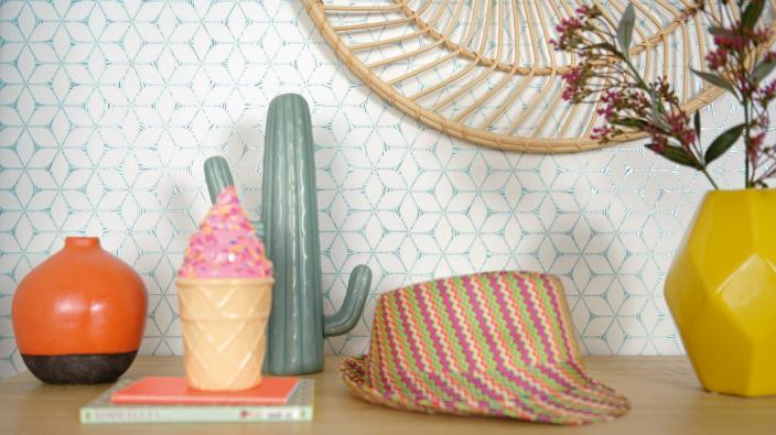 Wandgestaltung mit Vliestapete, graphisches Muster mit weiß-türkisem Kontrast, Sideboar mit farbiger Deko