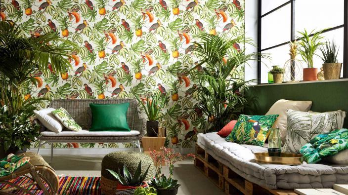 Wandgestaltung mit Vliestapete tropisches Muster, Wohnraum jung mit Sofa und vielen Grünpflanzen