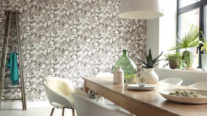 Wandgestaltung mit Vliestapete, tropisches Motiv in weiß-taupe, Esszimmer, großer Holzesstisch, weiße Stühle, Pflanzendeko