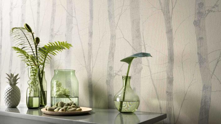 Wandgestaltung mit Vliestapete in blassem Silbergrau, Motiv Birkenstämme, Sideboard mit grüner Glasdeko und Grünpflanzen