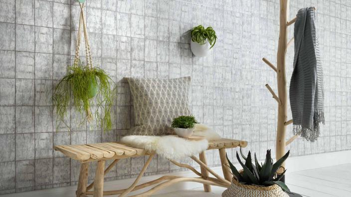 Wandgestaltung mit Vliestapete in hellem Blaugrau, Kachel-Look in Holzoptik, Flur mit natürlicher Holzbank, Kleiderständer aus Holz, Kissen und Korbdeko