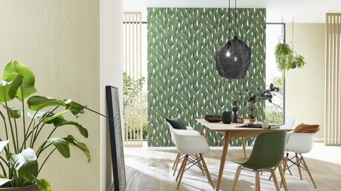 Modernes helles Esszimmer mit grüner Vliestapete mit Blattmuster, Esstisch und moderne Stühle