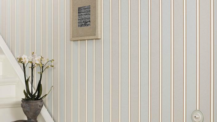 Flur mit weißer Treppe, klassische Streifen-Tapete in Ecru und Beige, Blumentopf mit weißen Blüten