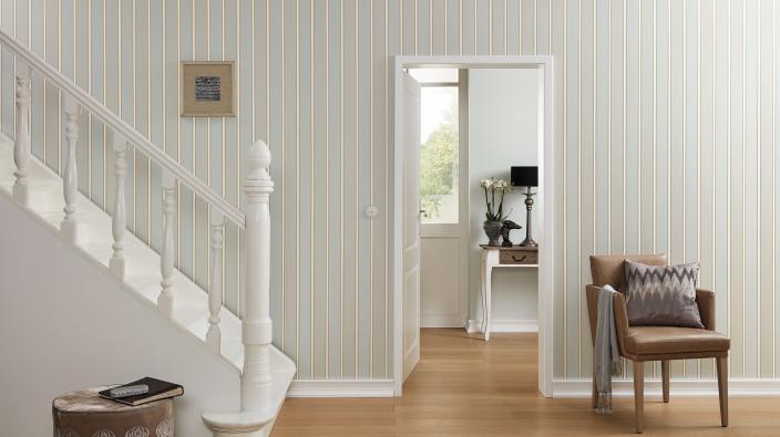 Flur mit weißer Treppe, klassische Streifen-Tapete in Ecru und Beige, brauner Ledersessel