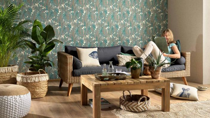 Wohnzimmer mit hellen Holzmöbeln und moderner Wandgestaltung mit Vliestapete im Dschungellook warmen Grün- und Beigetönen