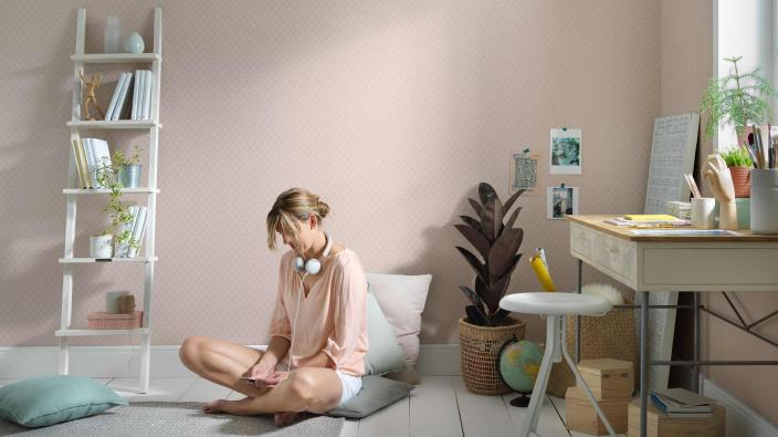 Modernes Arbeitszimmer, Vliestapete in rosa, heller Schreibtisch, Blonde junge Frau auf Sitzkissen
