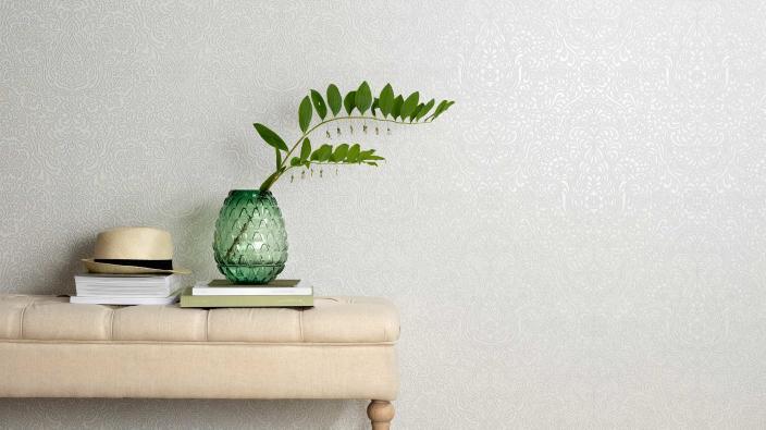 Wandgestaltung mit edler Vliestapete in weißem Ornamentmuster, Sitzbank in beige, Vase grün