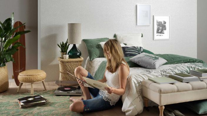 modernes Schlafzimmer in weiß und grün, Vliestapete mit weißem Muster, junge Frau mit Schallplattenspieler,
