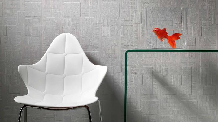 Tapete in hellgrauem Grafikmuster, überstreichbar, weißer Stuhl, Aquarium mit Goldfisch