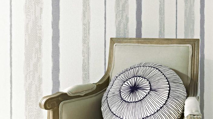 Antiker Sessel vor gestreifter Tapete in Grau