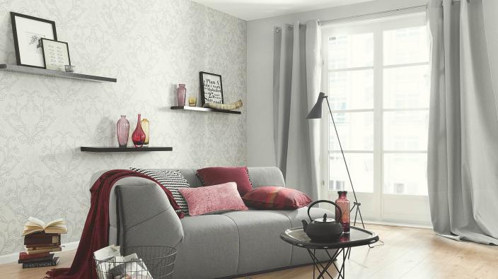 Junges Wohnzimmer mit hell grauer Tapete mit modernem Ornament, helles Sofa