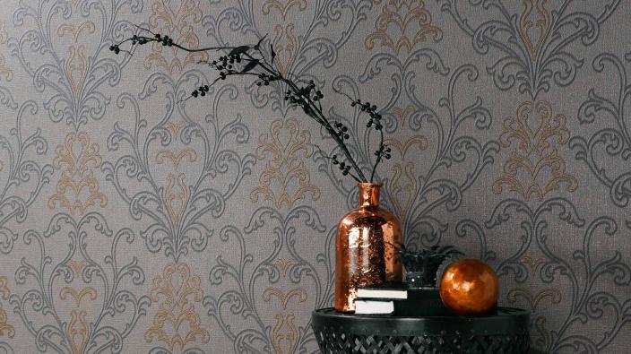 Tapete im Ethno-Look in Grau und Bronze mit modernem Ornament, Vase in Kupfer auf Beistelltisch