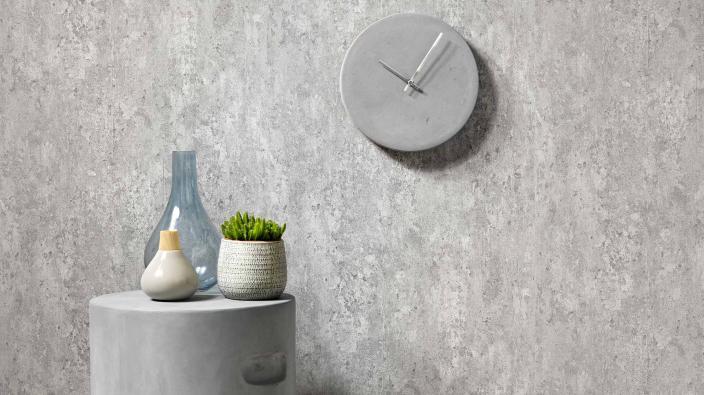 Vliestapete im Beton Look in einem hellen Grau, kleiner Betintisch mit Pflanzen und Vasen