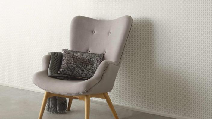 Sessel vor Wand mit Tapete mit hellem zierlichen Grafikmuster