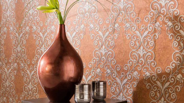 Vase in dunkler Bronze vor Tapete in Maronenbraun mit edlen Ornamenten