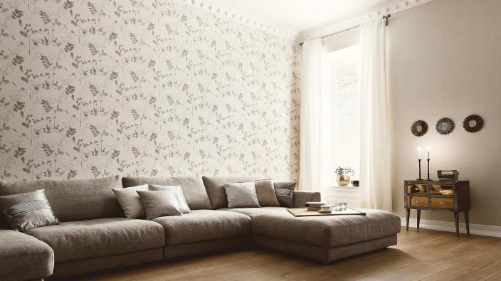 Wohnzimmer mit Couchlandschaft in Taupe, Tapete mit Blattmotiv