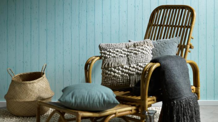 Wandgestaltung mit Vliestapeten skandinavisch, Holztapete in mint, Rattansessel, Kissen, Decke
