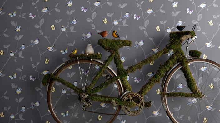 Vliestapete mit verspielten winzigen Vögeln, bunten Schmetterlingen und Blätterranken auf dunkelblauem Hintergrund
