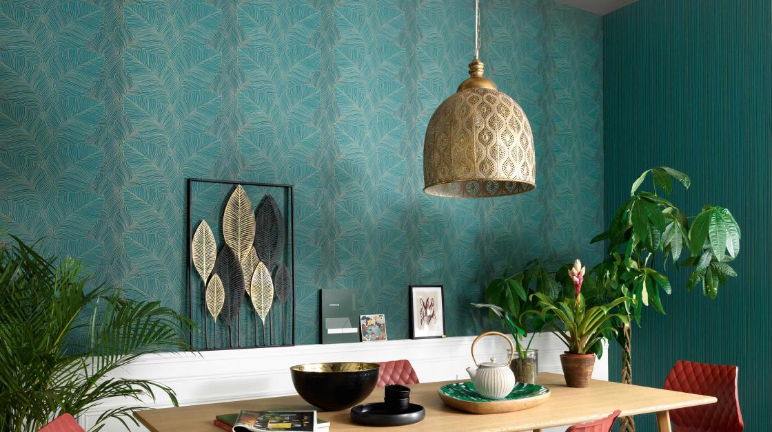 Green non-woven wallpaper with leaf motif Urban Jungle, dining room with table