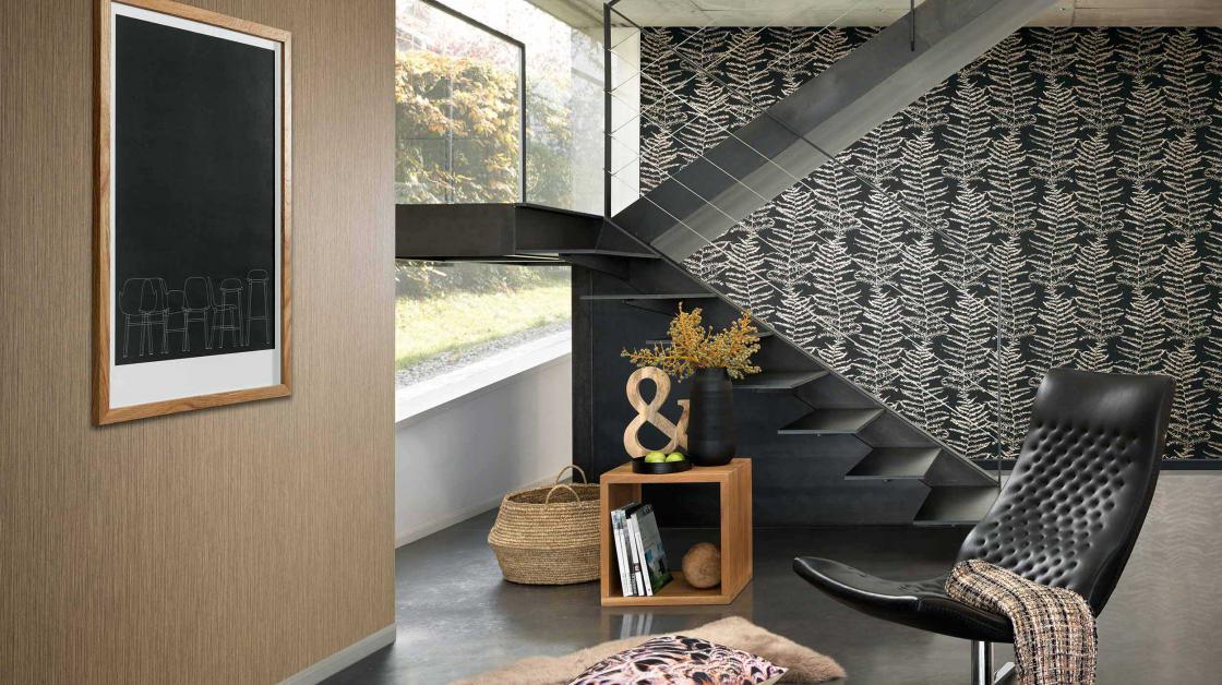 Moderner Wohnraum, Ledersessel, Treppe, Tapete in schwarz mit Farnmotiv