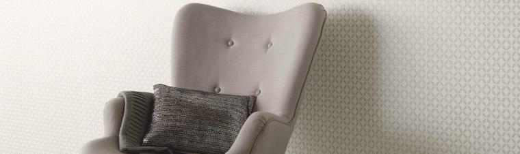 Moderner Sessel in Taupe vor Tapete mit zierlichem Grafikmuster in hellem Beige