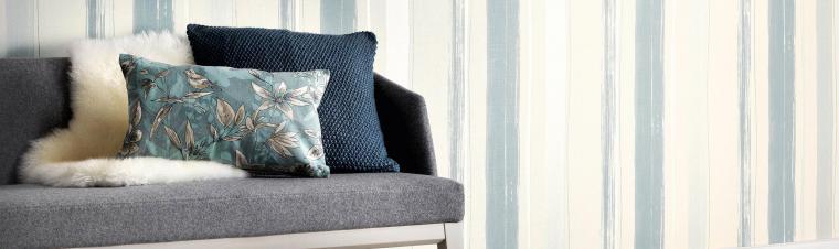 Streifentapete in Creme mit blauen verwaschenen Streifen, Sofa mit blauen Kissen