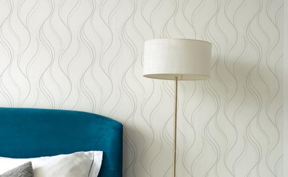Wandgestaltung Schlafzimmer, weiße Vliestapete mit Wellenmuster, Lampe und blaues Bett