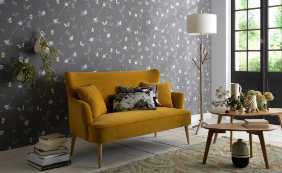 Vliestapete mit verspielten winzigen Vögeln, bunten Schmetterlingen und Blätterranken auf dunkelblauem Hintergrund. Senfgelbes Sofa im Vordergrund.