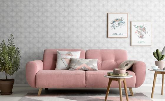 Vliestapete mit schwerelosem Grafikmuster in einem hellen Grau. Im Vordergrund rosanes Sofa im Scandi-Styl.