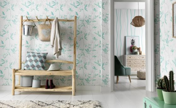 Vliestapete mit zarten Blattmotiven in leichtem Türkis. Im Hintergrund Tapete in modernem Wellenmotiv.
