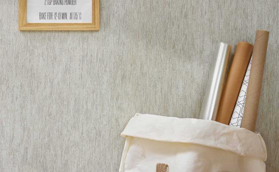 Vlietapete mit versteinert wirkender Holzrindenstruktur in einem hellen Grau
