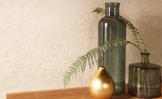 Vliestapete in einem zarten beige, die durch goldene metallic Effekte an der Wand wie Gold wirkt