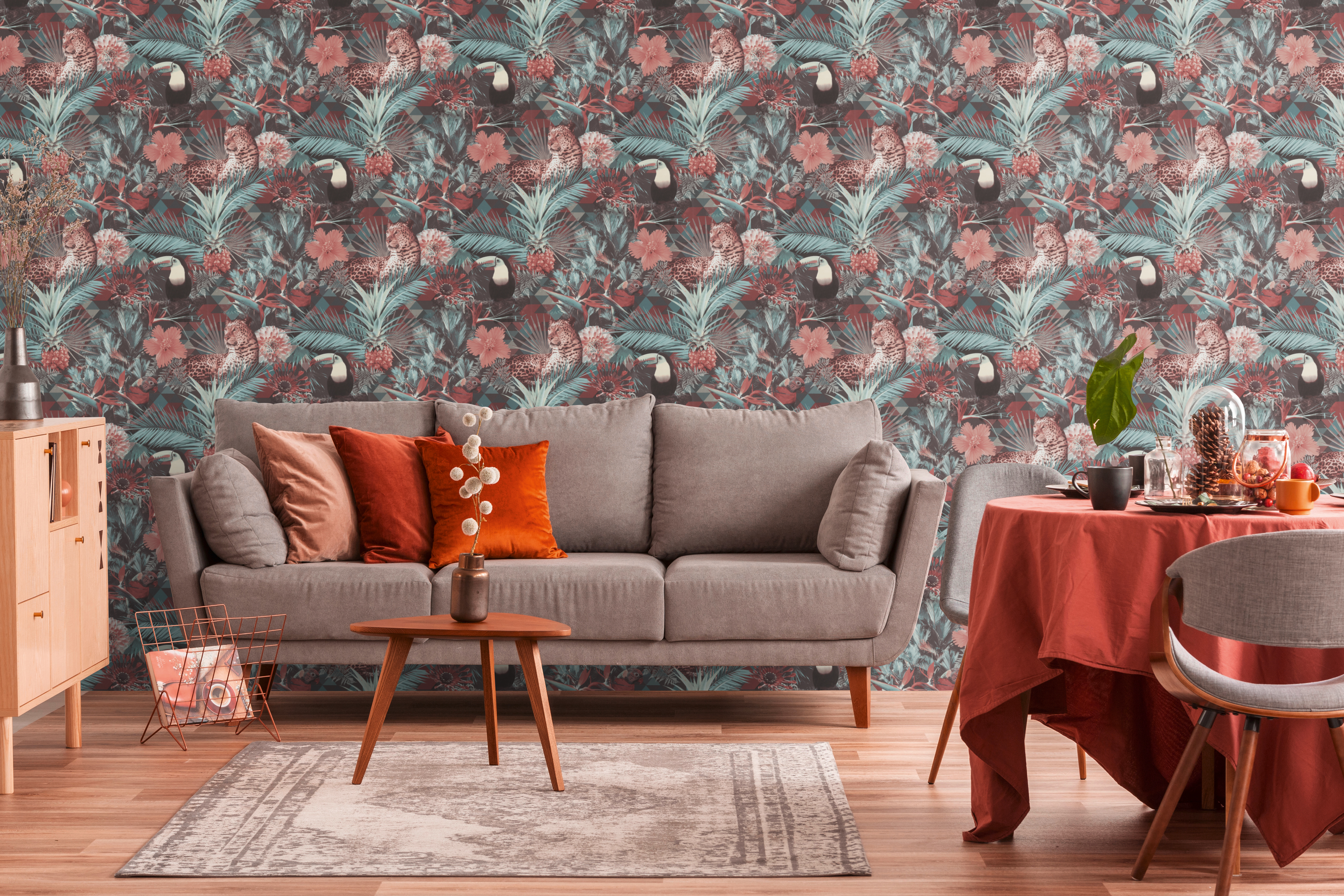 Wohnzimmer mit Sofa und Vliestapete mit Dschungelmotiv in Blau und Coralle